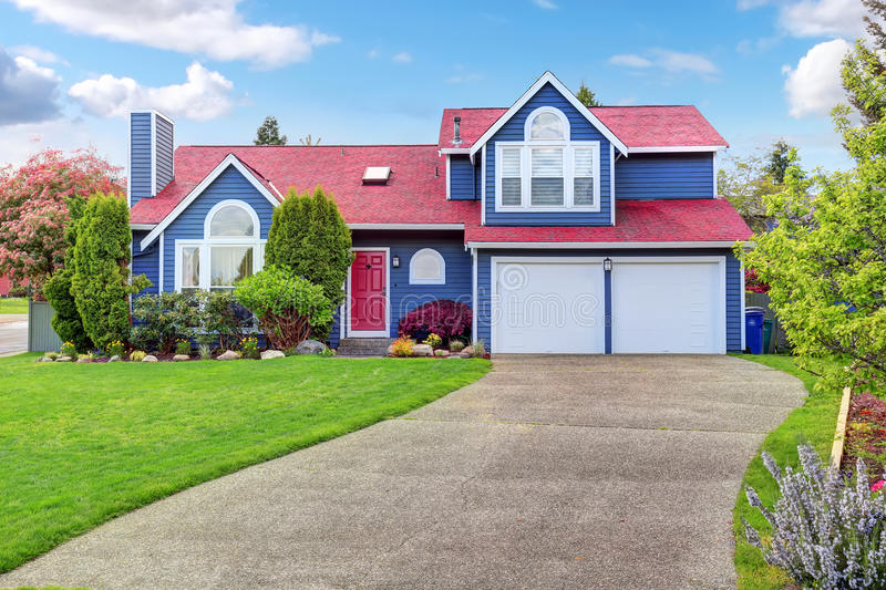 beautiful curb appeal with blue exterior paint and red roof stock