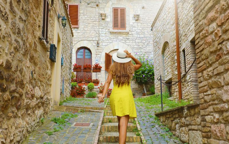 Beautiful curious young woman with yellow dress and hat goes upstairs in street in Assisi, Italy. Rear view of happy cheerful girl stock images