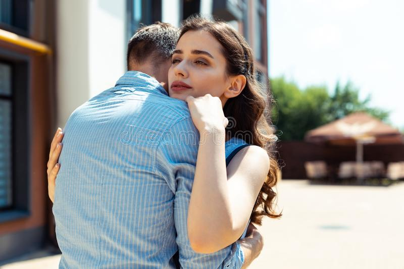Beautiful curly dark-haired wife hugging her supportive man. Curly dark-haired wife. Beautiful curly dark-haired wife hugging her supportive men standing outside royalty free stock images