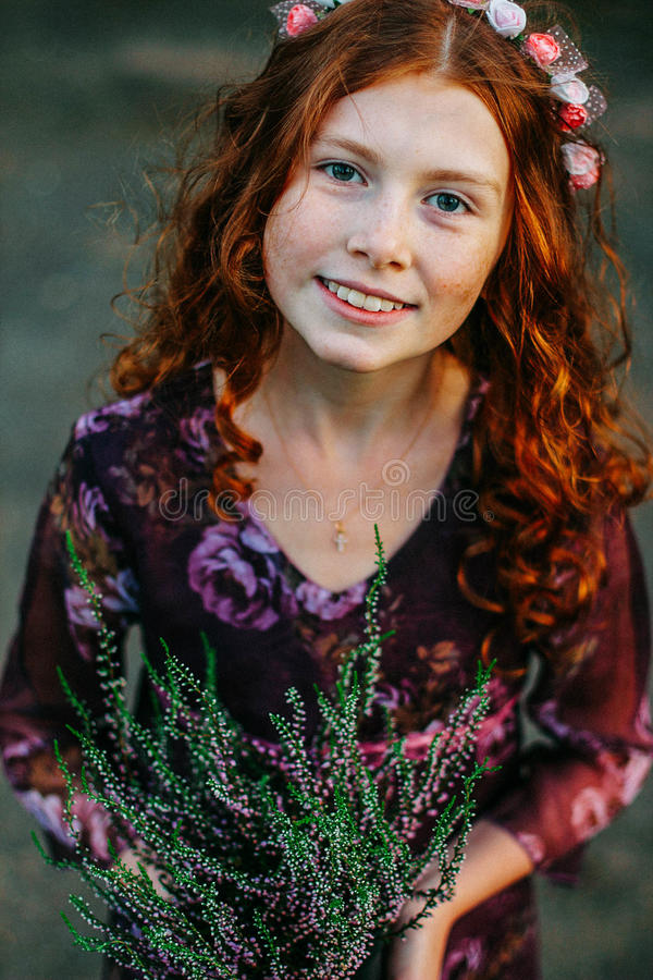 Beautiful curly girl holding flowering heather royalty free stock images