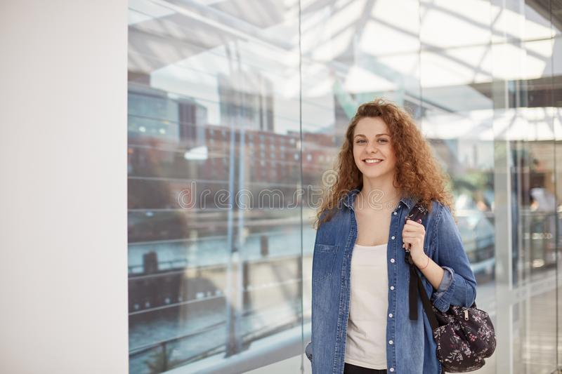 Beautiful curly girlfriend dressed in fashionable denim jacket, carries rucksack, strolls in shopping mall, buys necessary things, royalty free stock photos