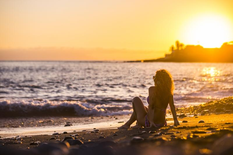 Beautiful curly hair nice model woman middle age young sitting at the beach enjoying the freedom and the relaxed sunset with royalty free stock images
