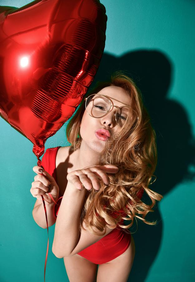 Beautiful curly hair young woman in clear aviator glasses hold big red star balloon blow kiss sign with lips on mint background stock image