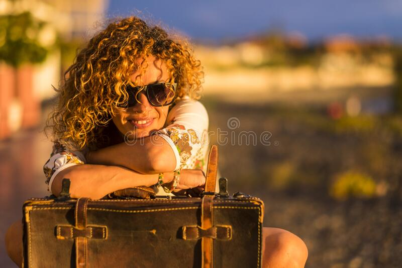 Beautiful curly hair young woman enjoy and relax outdoor with old luggage and smile - concept of travel and happy lifestyle with. Cheerful people - sunset time royalty free stock photos