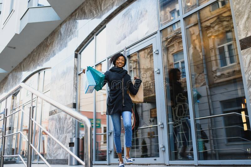 Beautiful curly haired afro-american woman standing in a shopping mall with coloured shopping bags in hands.  stock images