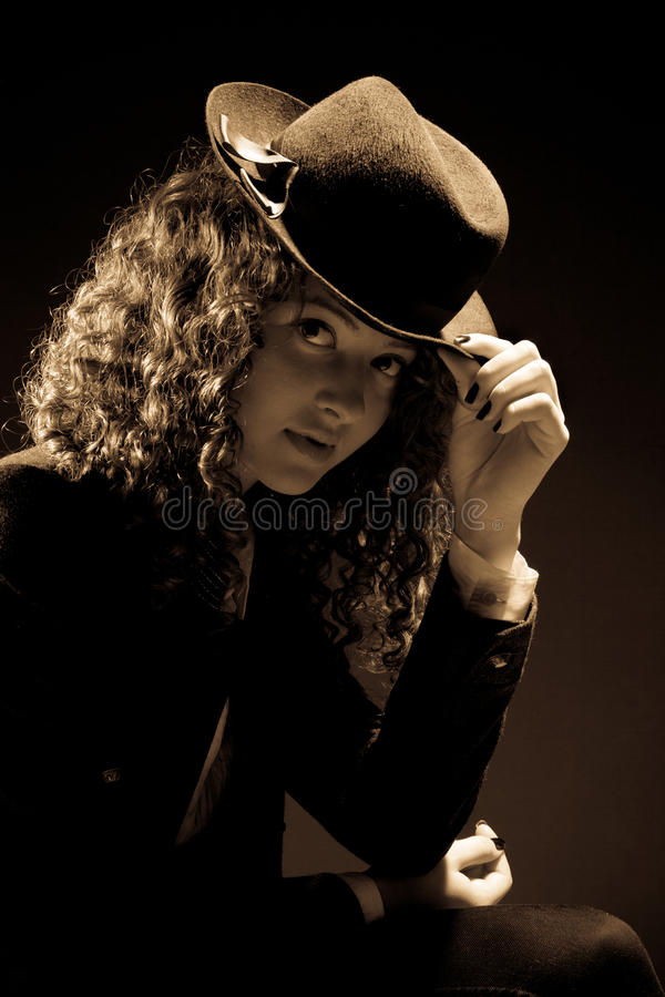 Beautiful curly-haired woman looking to the camera. Beautiful curly-haired woman in fedora looking to the camera stock photo