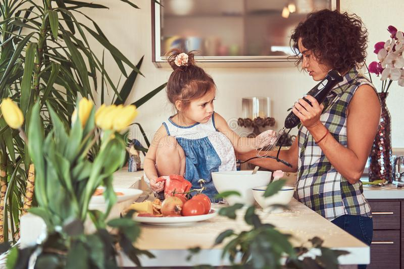 Beautiful Hispanic mother teaches her cute little daughter prepare pizza in the kitchen. stock photo