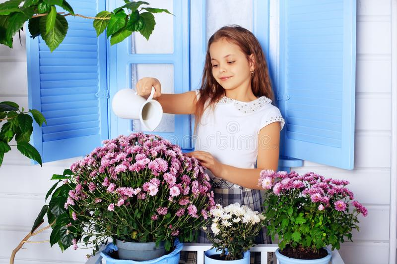 Beautiful curly little girl watering flowers. The concept of chi stock images