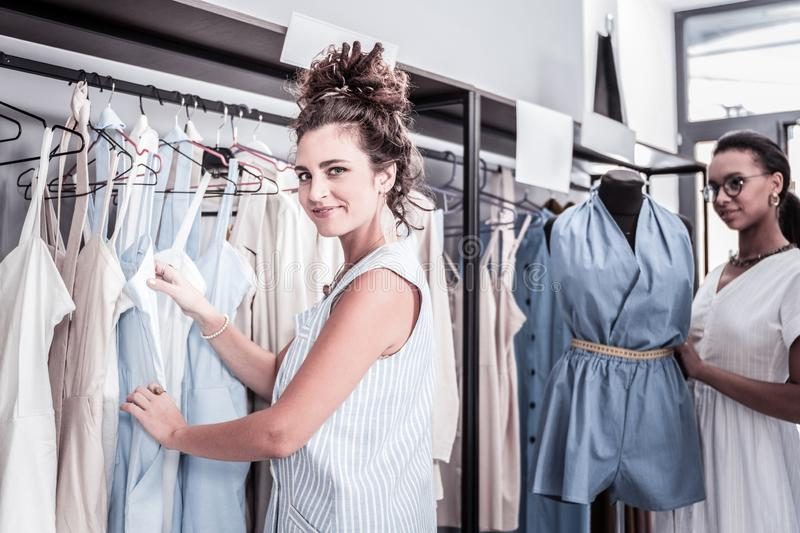 Beautiful curly woman with nice hair bun shopping in her favorite boutique. Favorite boutique. Beautiful curly women with nice hair bun feeling extremely stock photo