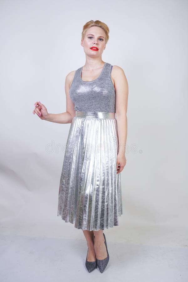 Beautiful curvy girl with short hair in silver tank top and metallic pleated skirt stands on white background in Studio. blonde pl stock photo