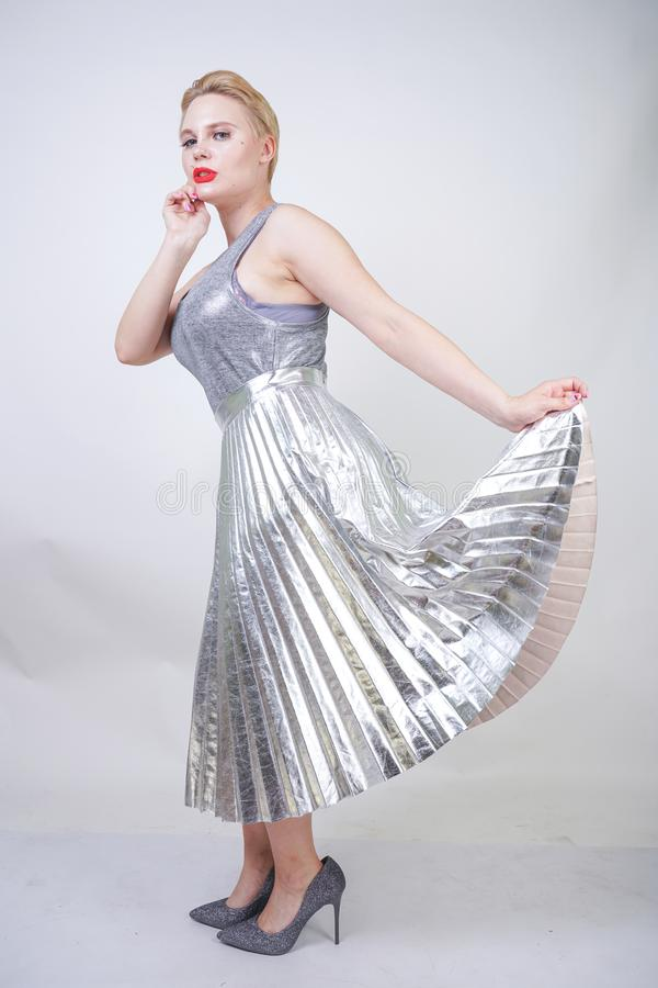 Beautiful curvy girl with short hair in silver tank top and metallic pleated skirt stands on white background in Studio. blonde pl stock images
