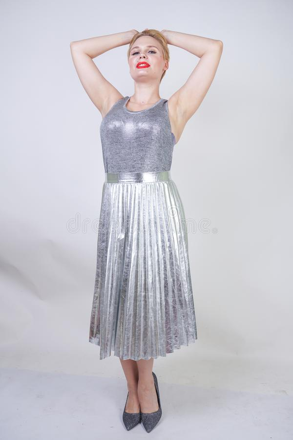 Beautiful curvy girl with short hair in silver tank top and metallic pleated skirt stands on white background in Studio. blonde pl stock image