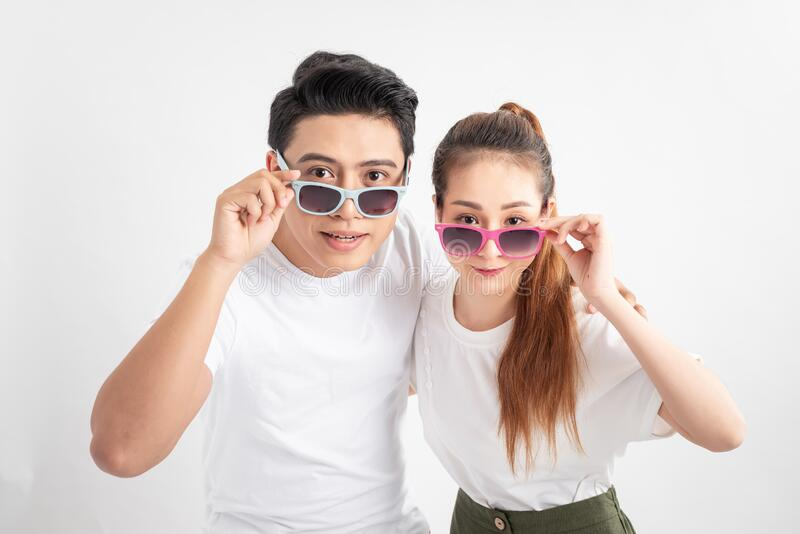 Beautiful cute adorable surprised couple putting colorful spectacles down showing wow emotion over yellow background, isolated.  stock photography