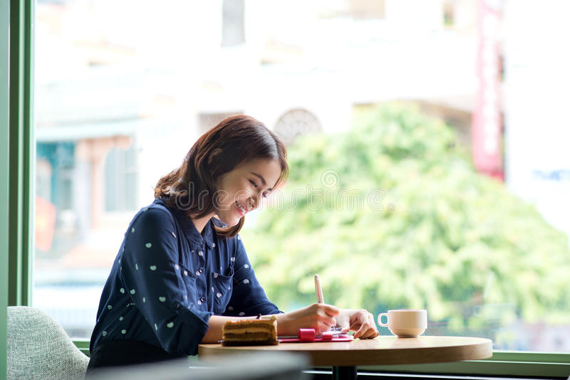 Beautiful cute asian young businesswoman in the cafe. And drinking coffee smiling stock image