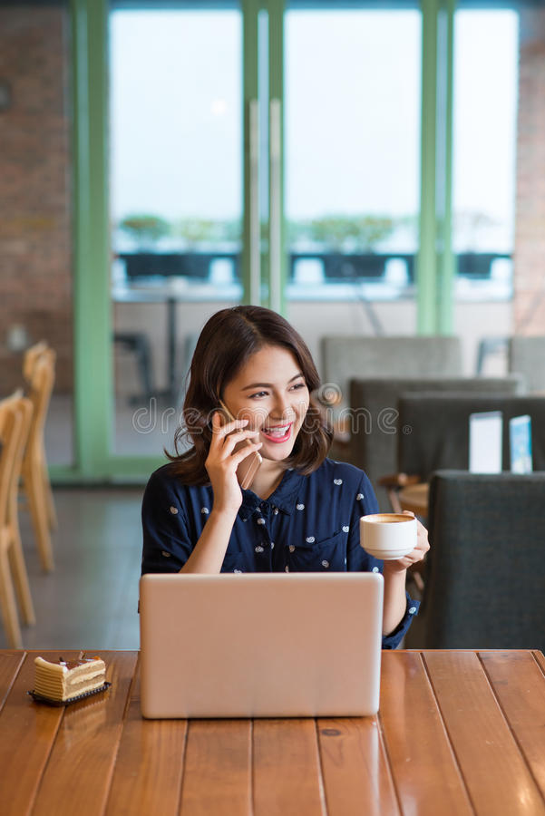 Beautiful cute asian young businesswoman in the cafe, listening. To mobile phone and holding coffee mug royalty free stock images