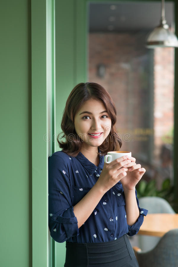 Beautiful cute asian young businesswoman in the cafe, listening. To mobile phone and holding coffee mug royalty free stock image