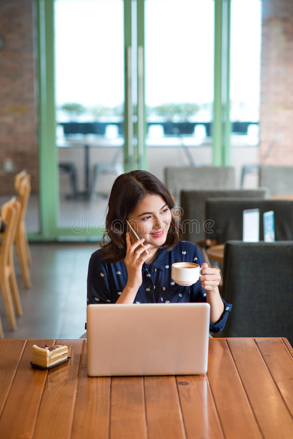 Beautiful cute asian young businesswoman in the cafe, listening. To mobile phone and holding coffee mug stock photography