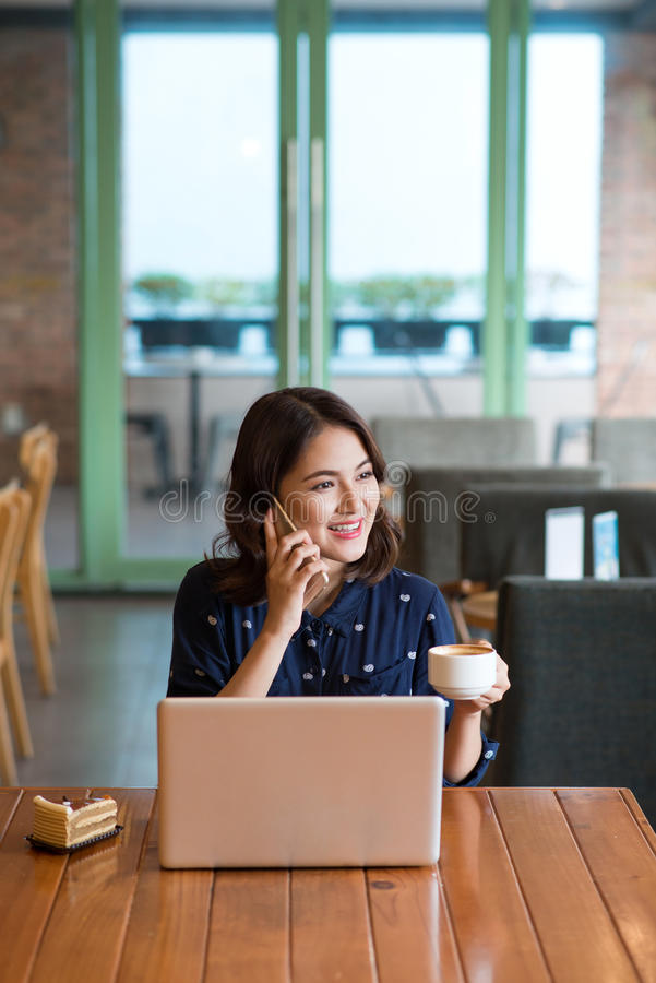 Beautiful cute asian young businesswoman in the cafe, listening. To mobile phone and holding coffee mug stock photos
