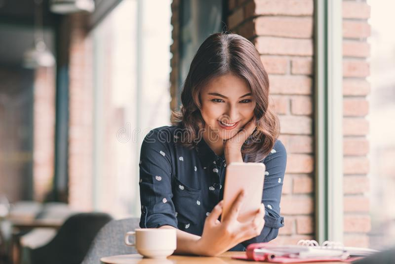 Beautiful cute asian young businesswoman in the cafe, taking selfie photo by mobile phone stock images