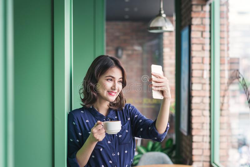 Beautiful cute asian young businesswoman in the cafe, taking selfie photo by mobile phone royalty free stock image