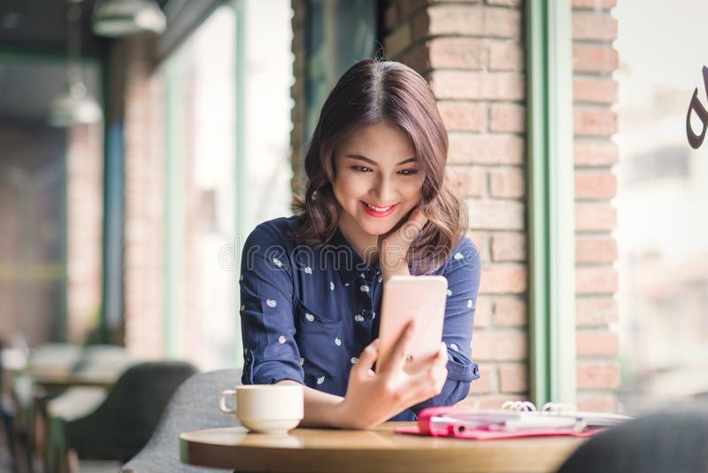 Beautiful cute asian young businesswoman in the cafe, taking selfie photo by mobile phone stock photo