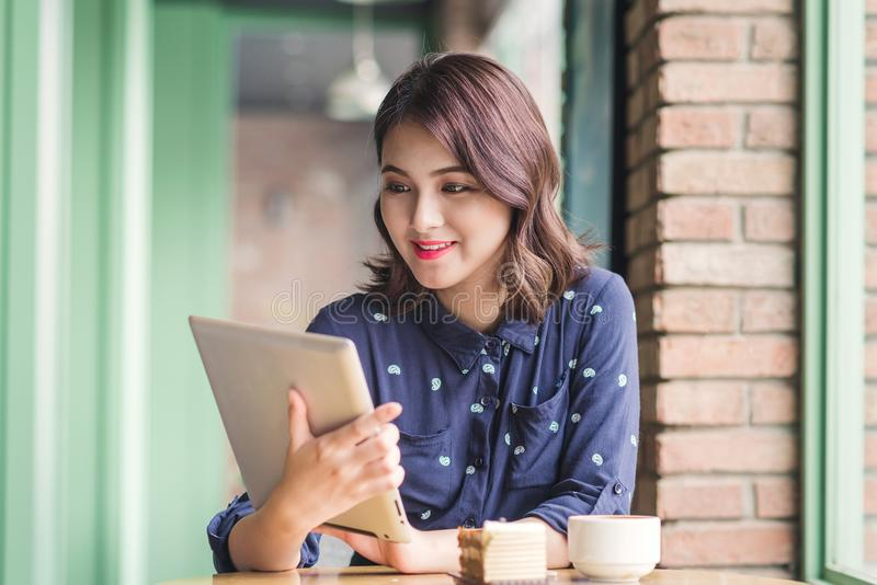 Beautiful cute asian young businesswoman in the cafe, using digital tablet and drinking coffee smiling royalty free stock photos