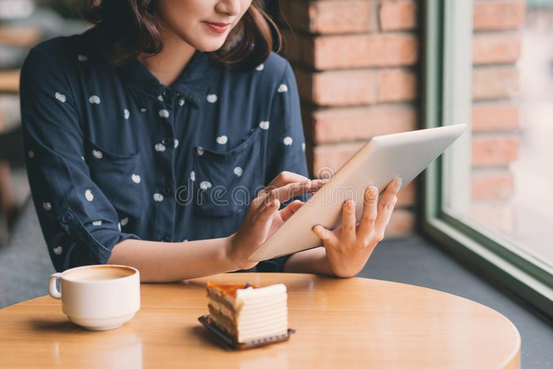 Beautiful cute asian young businesswoman in the cafe, using digital tablet and drinking coffee smiling royalty free stock images
