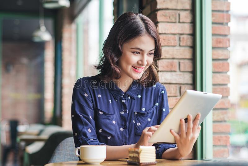 Beautiful cute asian young businesswoman in the cafe, using digital tablet and drinking coffee smiling stock photo