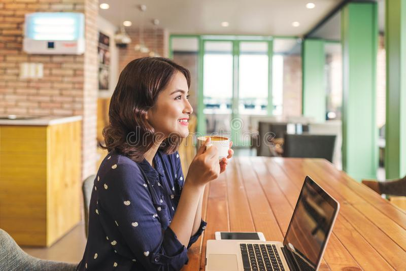Beautiful cute asian young businesswoman in the cafe, using laptop and drinking coffee smiling royalty free stock images