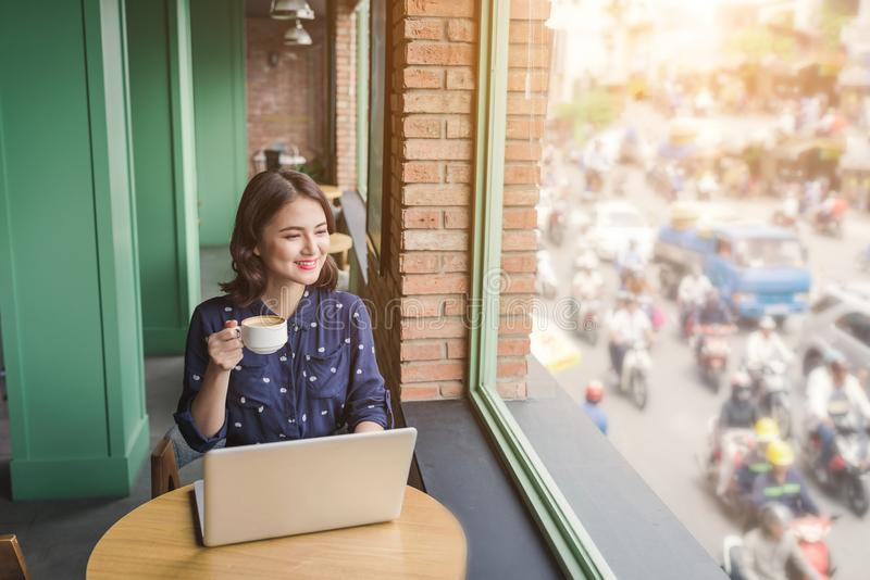 Beautiful cute asian young businesswoman in the cafe, using laptop and drinking coffee smiling royalty free stock photography