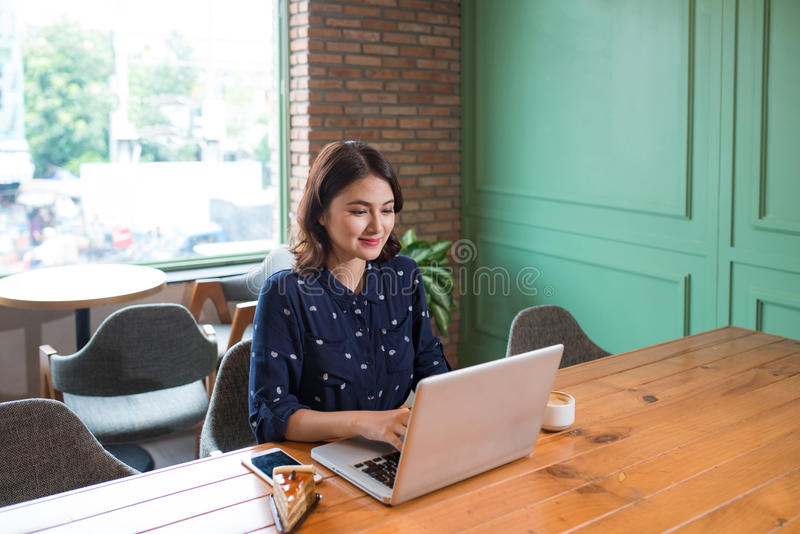 Beautiful cute asian young businesswoman in the cafe, using laptop and drinking coffee smiling stock photo