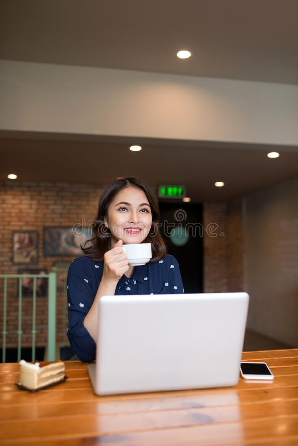 Beautiful cute asian young businesswoman in the cafe, using laptop and drinking coffee smiling stock photography