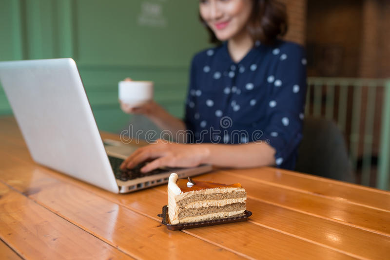 Beautiful cute asian young businesswoman in the cafe, using lapt. Op and drinking coffee smiling stock photography