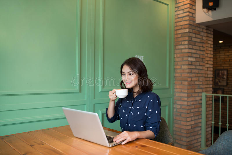 Beautiful cute asian young businesswoman in the cafe, using laptop and drinking coffee smiling stock photos