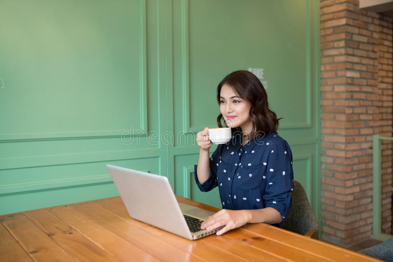 Beautiful cute asian young businesswoman in the cafe, using laptop and drinking coffee smiling stock images