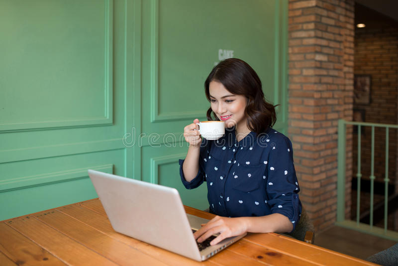 Beautiful cute asian young businesswoman in the cafe, using laptop and drinking coffee smiling stock image