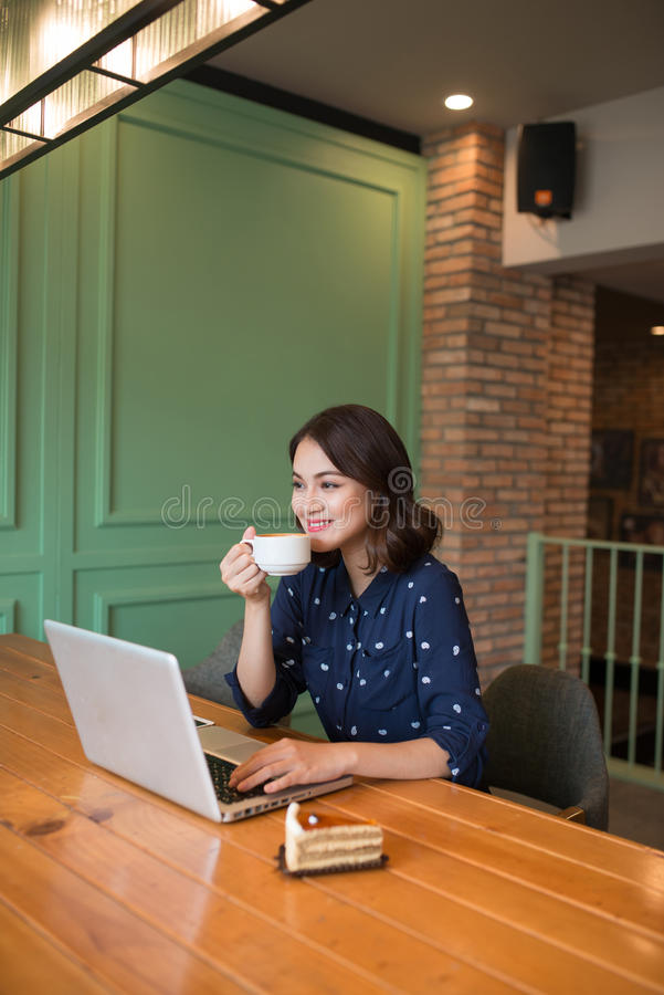 Beautiful cute asian young businesswoman in the cafe, using laptop and drinking coffee smiling royalty free stock photos