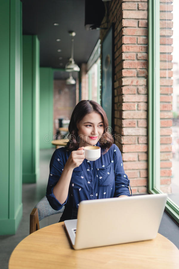 Beautiful cute asian young businesswoman in the cafe, using laptop and drinking coffee smiling royalty free stock image