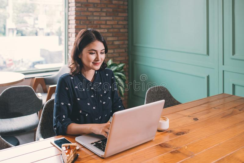 Beautiful cute asian young businesswoman in the cafe, using laptop and drinking coffee smiling royalty free stock photo