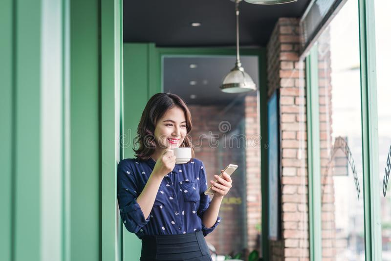 Beautiful cute asian young businesswoman in the cafe, using mobile phone and drinking coffee smiling stock images