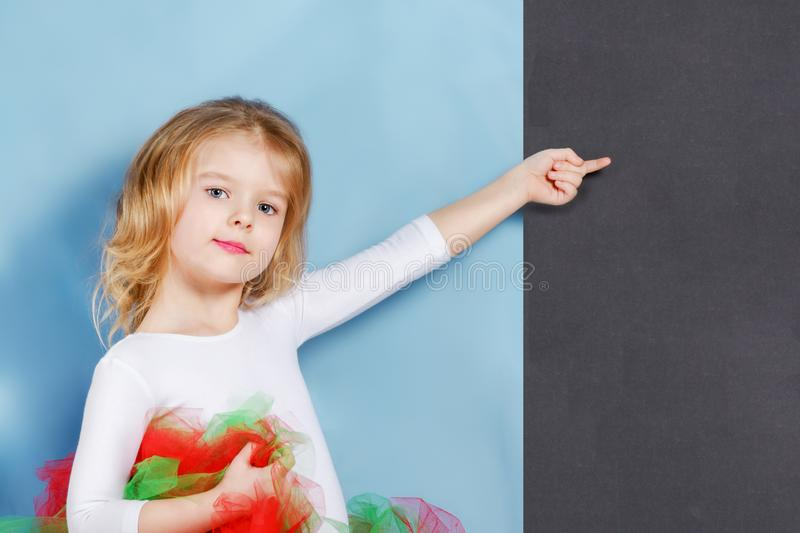 Beautiful cute baby posed. A little girl with blond hair points her finger at a blank space on a black background. Light advertising picture stock photos