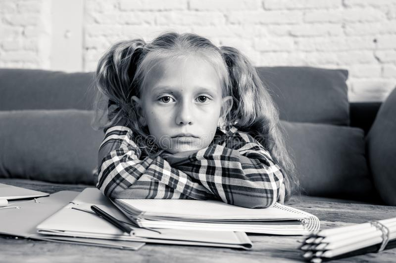 Beautiful cute blonde 9 years elementary student feeling sad bored and a overwhelmed trying to study at home in learning royalty free stock photography