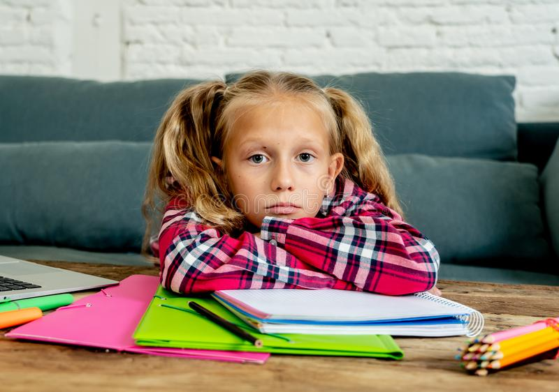 Beautiful cute blonde 9 years elementary student feeling sad bored and a overwhelmed trying to study at home in learning stock image