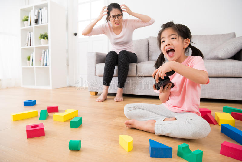 Excited daughter playing video games by controller royalty free stock images