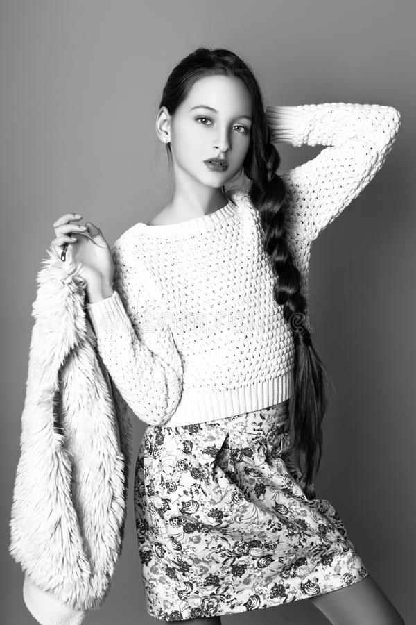 Beautiful Cute fashion girl teenage in a sweater and a skirt with long hair posing in studio. Black and white photo royalty free stock photos