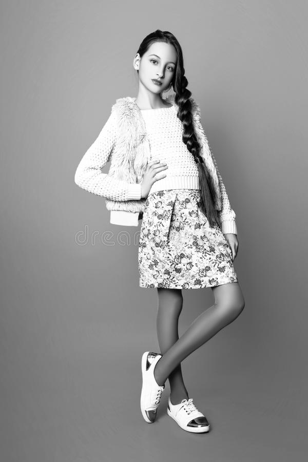Beautiful Cute fashion girl teenage in a sweater and a skirt with long hair posing in studio. Black and white photo stock photography