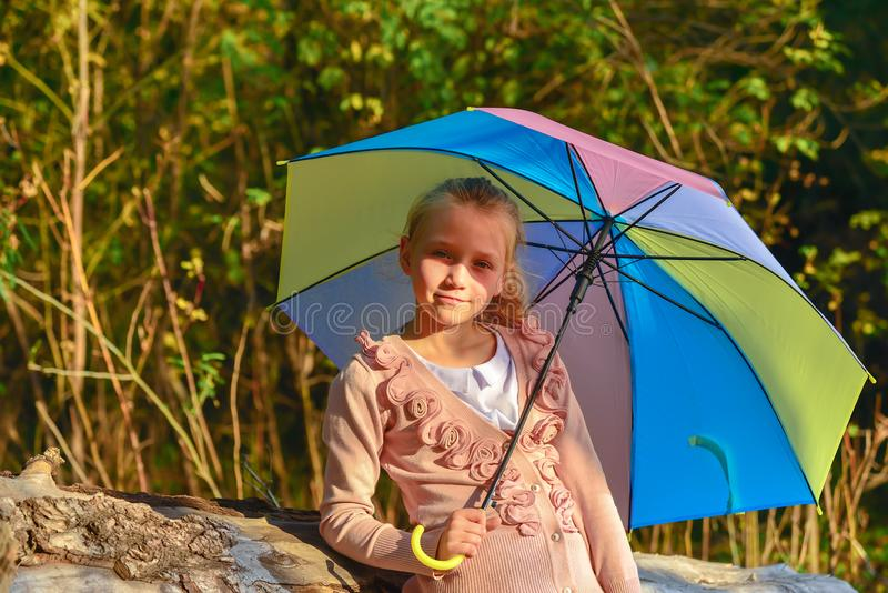 Beautiful and cute girl with a color umbrella in the fall in the park, portrait of a girl under the autumn evening sun stock photo