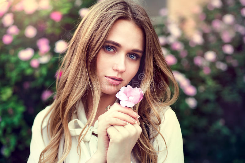 Beautiful cute girl holding rose flower in hands close to her face at sunset time royalty free stock photo