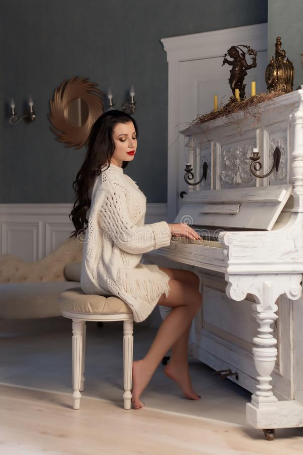 Beautiful cute girl in white warm jacket at home playing on old piano stock photos