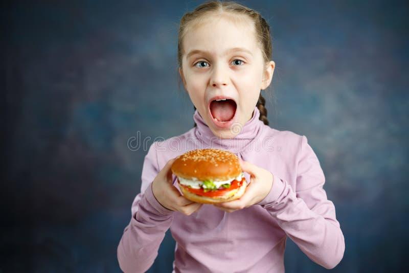 Beautiful Cute Little Caucasian Blond Girl With Hamburger stock image